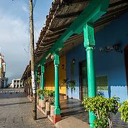 A view of some of the brightly painted buildings lining Independence Square, looking towards Parque Central and Granada Cathedral. Parque Central is the main square and the historic heart of Granada, Nicaragua.