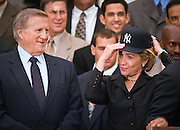 First lady Hillary Rodham Clinton, wearing a New York Yankees baseball cap smiles as she poses for a photo with Yankees owner George M. Steinbrenner III (L) and the team as the 1998 World Series winning Yankees visited the White House June 10, 1999 in Washington, DC.