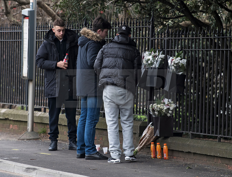 © Licensed to London News Pictures. 27/01/2018. London, UK. A group of young men place three Lucozade drinks bottles at the scene where three teenage pedestrians were killed near a bus stop in Hayes, West London after a black Audi car is believed to have collided with them. Police were called to the incident, on Friday night at 20:41hrs, close to the M4 Junction 4 following reports of a serious road traffic collision. The victims died at the scene - are all believed to be teenage males, aged approximately 16. Photo credit: Ben Cawthra/LNP