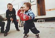 Toddler with boxing gloves, Winterbourne travellers site, Bristol, UK, 1990's