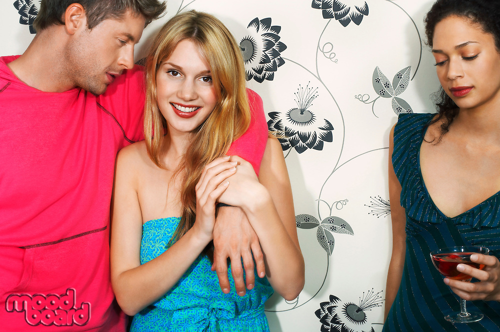 Young woman with friends by floral print wall portrait