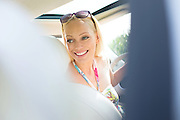 Happy beautiful woman looking back while driving car