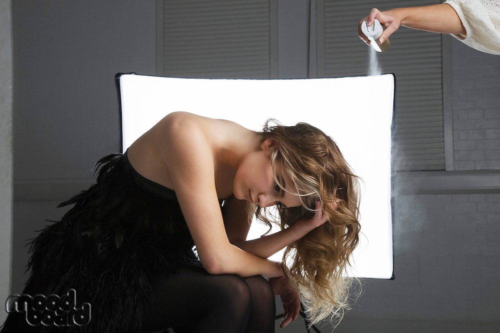 Hairstylist spraying hair product on female model's hair