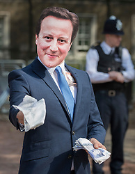 © Licensed to London News Pictures. 12/05/2016. London, UK. Police standby as a protestor dressed as Prime Minister David Cameron offers fake money as he stands outside the anti-corruption summit. The real Mr Cameron is hosting a one day summit which is addressing world corruption. Photo credit: Peter Macdiarmid/LNP
