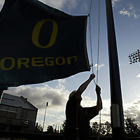 Oregon Ducks football team prepares for trip and travels to Oklahoma for game against against the Sooners. Staffer lowers flag at end of day outside stadium at Oregon...Photos © Todd Bigelow/Aurora