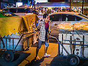 26 MAY 2016 - BANGKOK, THAILAND: A vendor at the Silom Road night market pushes the carts that contain his merchandise down Silom Road. The night market on Silom Road, close to Bangkok's famous Patpong tourist area, is being closed by the Bangkok municipal government. Vendors have been told they have to leave the sidewalk on Silom Road by the end of May, 2016. The market is the latest street market being shut down by city officials as a part of the government's plan to clean up Bangkok. The Silom Road night market sells mostly tourist oriented clothes, inexpensive Thai art, and bootleg movies on DVD.       PHOTO BY JACK KURTZ