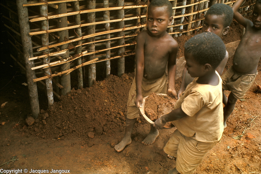 Village life in Africa: West Africa, Liberia, Kpelle (Guerze) tribe: children carrying mud, helping in the construction of a wattle-and-daub house.