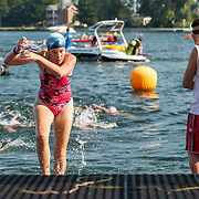 A swimmer runs out before the other participants, removing her glasses.