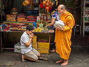 28 AUGUST 2015 - BANGKOK, THAILAND: A Theravada Buddhist monk prays with a person who made merit in Bangkok's Chinatown. Mahayana  Buddhists believe that the gates of hell are opened on the full moon of the seventh lunar month of the Chinese calendar, and the spirits of hungry ghosts allowed to roam the earth. These ghosts need food and merit to find their way back to their own. People help by offering food, paper money, candles and flowers, making merit of their own in the process. Hungry Ghost Day is observed in communities with a large ethnic Chinese population, like Bangkok's Chinatown.       PHOTO BY JACK KURTZ