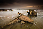 Boat wreck exposed at low tide in a moody sunset, near Church Bay (Porth Swtan) North Anglesey. Holyhead mountain is the large hill in the background, situated on Holy Island.