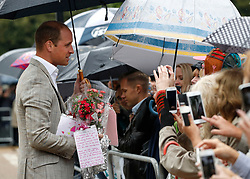 The Duke of Cambridge is given flowers by members of the public which he then placed amongst the tributes to Diana, Princess of Wales attached to the Golden Gates of Kensington Palace, London, ahead of the 20th anniversary of his mother's death.