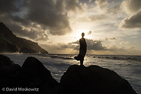 Darcy Ottey contemplates the universe from an oceanside perch. Kauai, Napali Coast