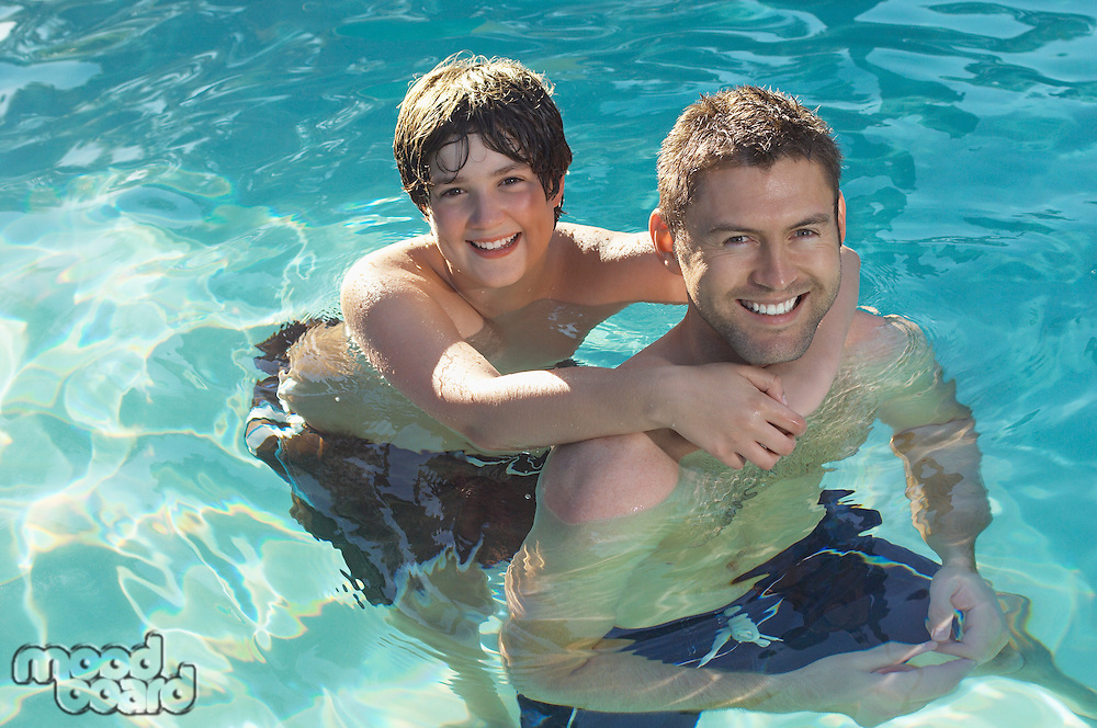 Father giving son piggy back in swimming pool, portrait