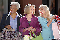 Smiling Women walking outside carrying bags on Shopping Trip