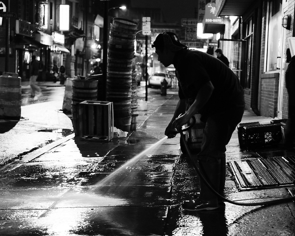 The sidewalk outside of a Chinatown fish market is hosed down late at night.