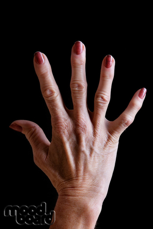 Senior woman's hand with red nail polish against black background