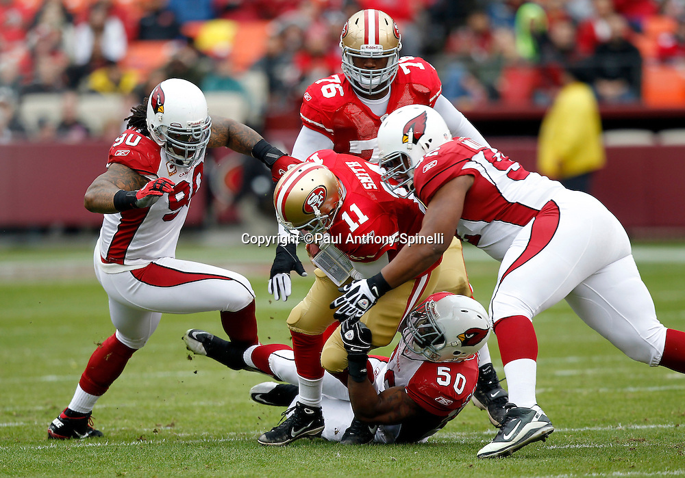 San Francisco 49ers quarterback Alex Smith (11) gets gang tackled by Arizona Cardinals linebacker O'Brien Schofield (50), Arizona Cardinals linebacker Cyril Obiozor (52), and Arizona Cardinals defensive tackle Darnell Dockett (90) during the first quarter of the NFL week 17 football game against the Arizona Cardinals on Sunday, January 2, 2011 in San Francisco, California. The 49ers won the game 38-7. (©Paul Anthony Spinelli)
