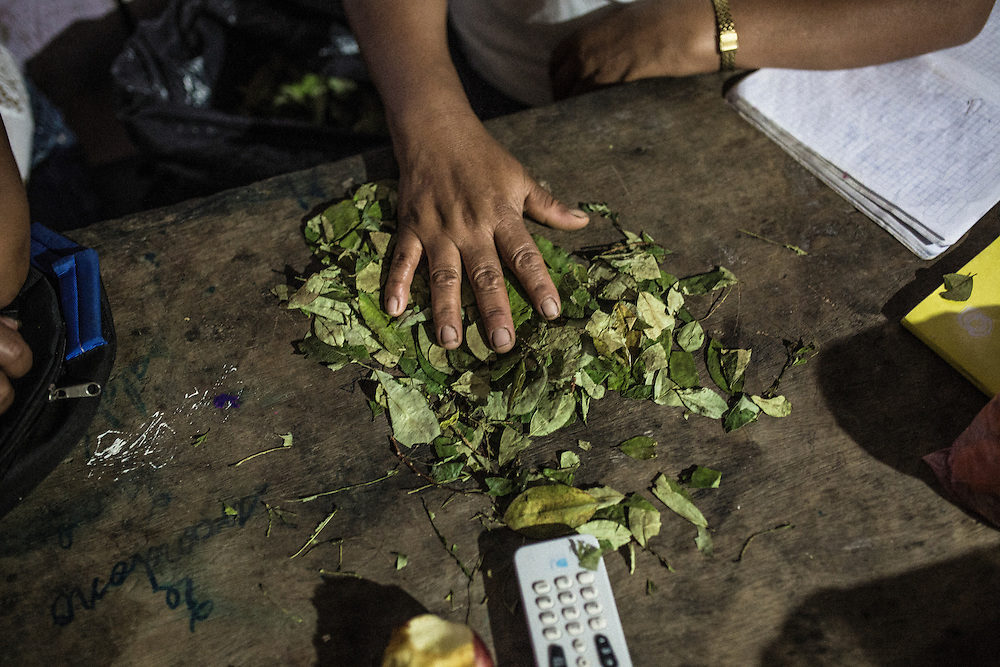 Its night in the village Unido Mantaro. On a table in a local restaurant lays a pile of coca leaves.
