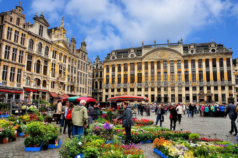 Flower Market and Guildhalls at Grand Place in Brussels, Belgium <br /> These 17th century guildhalls are a few of the magnificent buildings surrounding Grote Markt or La Grand Place in Brussels. The beautiful flowers are sold daily in the market.  However, every other August since 1971, this square is adorned with a million fragrant flowers creating a 252 by 78 foot blanket with complicated designs. The event is called the Flower Carpet festival.