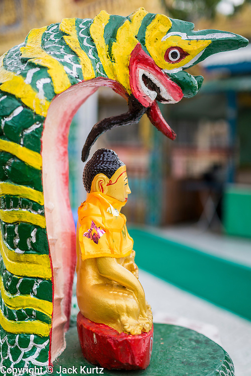 04 JUNE 2014 - YANGON, YANGON REGION, MYANMAR: A statue of the Buddha protected by a naga (mythical serpent who guards the Buddha) at Botataung Paya (Pagoda) in Yangon, Myanmar (Rangoon, Burma). Botataung is one of the most famous pagodas in Yangon with maze like interior of gold leaf covered walls. The pagoda houses a hair from the Buddha and is one of the most sacred sites in Burma. Yangon, with a population of over five million, continues to be the country's largest city and the most important commercial center.     PHOTO BY JACK KURTZ