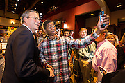 Former Florida Governor and potential Republican presidential candidate Jeb Bush takes a selfie with a young supporter at an early morning GOP breakfast event March 18, 2015 in Myrtle Beach, South Carolina.