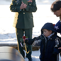 Five-year-old William Scott Dykman, son of the late Sgt. Scott Dykman, places a rose on his father's casket with the help of his mother, Chantell Russel Dykman, near Harrison, Mont. Scott Dykman a graduate of Harrison High School died as the result of a roadside bomb while serving in Iraq.