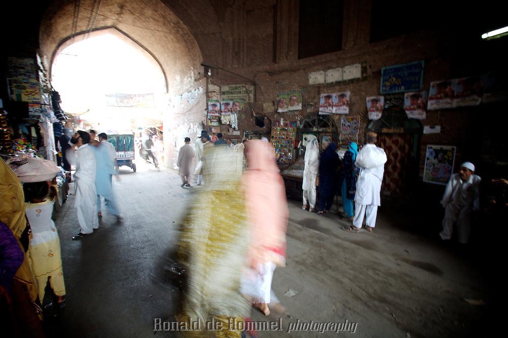 2007-08-13 Lahore, Pakistan. Women walking in the bazar in Lahore under an arch of one of the entrance gates.