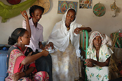 """Left to right, Domos, 17, Elen Milash, from the local branch of the Womens Union, """"Hamade"""", the administrator for peace village, Tsion, a former soldier with EPLF and  far right, Tiblets Keleta, 54, a recipient of a donkey enjoy the ceremonial Eritrean coffee ritual called """"Daga"""" which means sweet in the Kunama language August 24, 2006 in the district of Zoba Fithi which stands for """"Justice"""" in the southern region of Barentu, Eritrea.    (Photo by Ami Vitale)"""