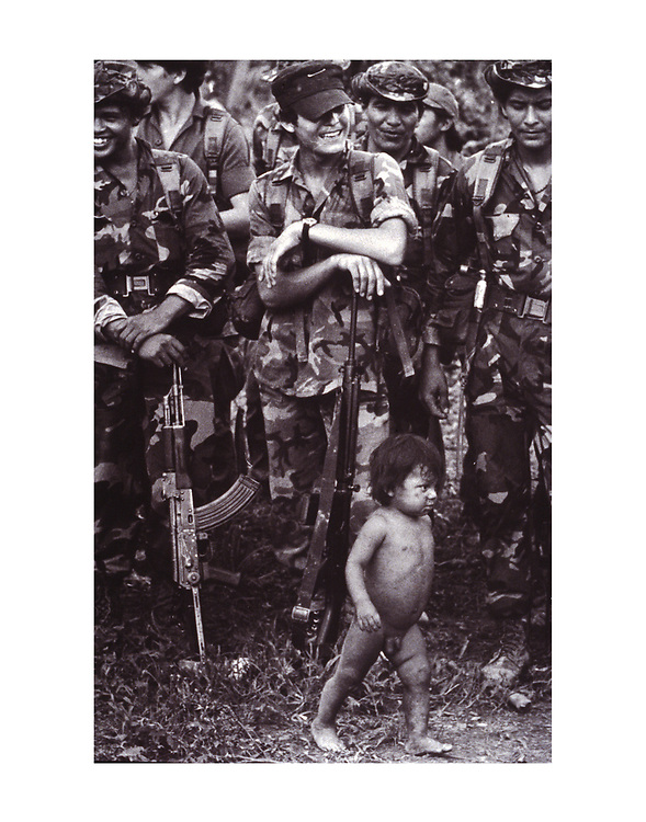 A naked Nicaraguan contra baby parades in front of a group of assembled troops at a base camp in southern Honduras. 1987