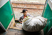15 JUNE 2013 - YANGON, MYANMAR:  A woman gets off the Yangon Circular Train with a bag of vegetables she hopes to sell. Yangon Circular Railway is the local commuter rail network that serves the Yangon metropolitan area. Operated by Myanmar Railways, the 45.9-kilometre (28.5 mi) 39-station loop system connects satellite towns and suburban areas to the city. The railway has about 200 coaches, runs 20 times and sells 100,000 to 150,000 tickets daily. The loop, which takes about three hours to complete, is a popular for tourists to see a cross section of life in Yangon. The trains from 3:45 am to 10:15 pm daily. The cost of a ticket for a distance of 15 miles is ten kyats (~nine US cents), and that for over 15 miles is twenty kyats (~18 US cents). Foreigners pay 1 USD (Kyat not accepted), regardless of the length of the journey.     PHOTO BY JACK KURTZ