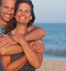 all American Couple with arms wrapped  around on another at the beach