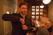 New York, NY, Sept. 10....shots of the restaurant Estela. Sommelier Thomas Carter uncorking a bottle of wine for diners. Behind him is a dining nook and wine on display.