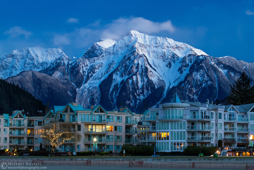 Late evening light on the Mount Cheam Range (Knight, Lady and Cheam Peaks) and the beach front condominiums at Harrison Hot Springs, British Columbia, Canada