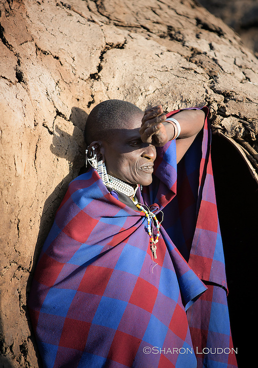 Maasai woman shields her eyes from the strong midday sun