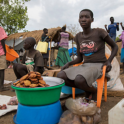 Joyce, 17, a refugee from South Sudan, sells food at a street market at the Bidi Bidi refugee settlement in Uganda. <br /> &quot;I want to buy soap,&quot; she says when asked about the reason why she is working. Refugees receive food at the camp but not soap, which they have to buy themselves.<br /> In one day she makes about 5000 Ugandan shillings, close to $1.50.