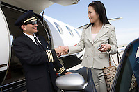 Mid-adult businesswoman shaking hands with pilot outside of private jet.