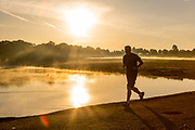 UNITED KINGDOM, Richmond Park: 14 May 2019 <br /> An early morning jogger makes his way through Richmond Park this morning as the sun rises on another fine day of weather across The UK. Temperatures are set to reach 19C in the capital and potentially higher in the Midlands.