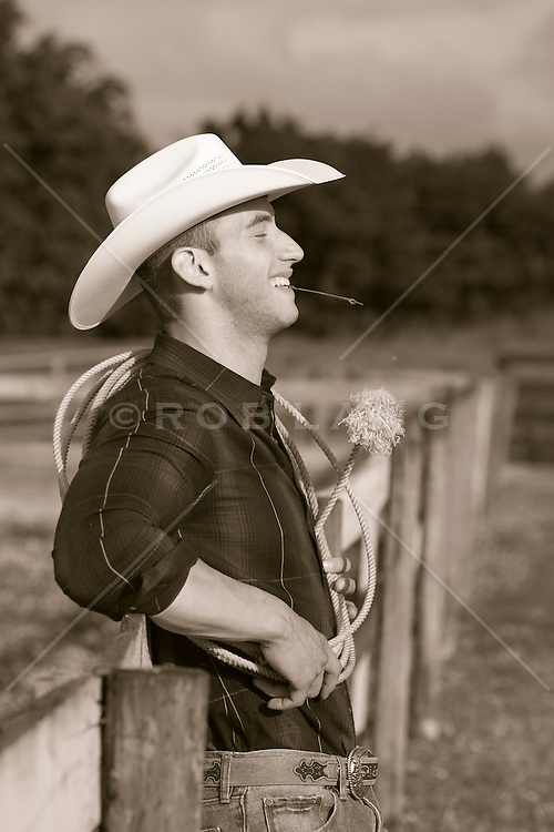 cowboy leaning against a fence with a blade of grass in his mouth