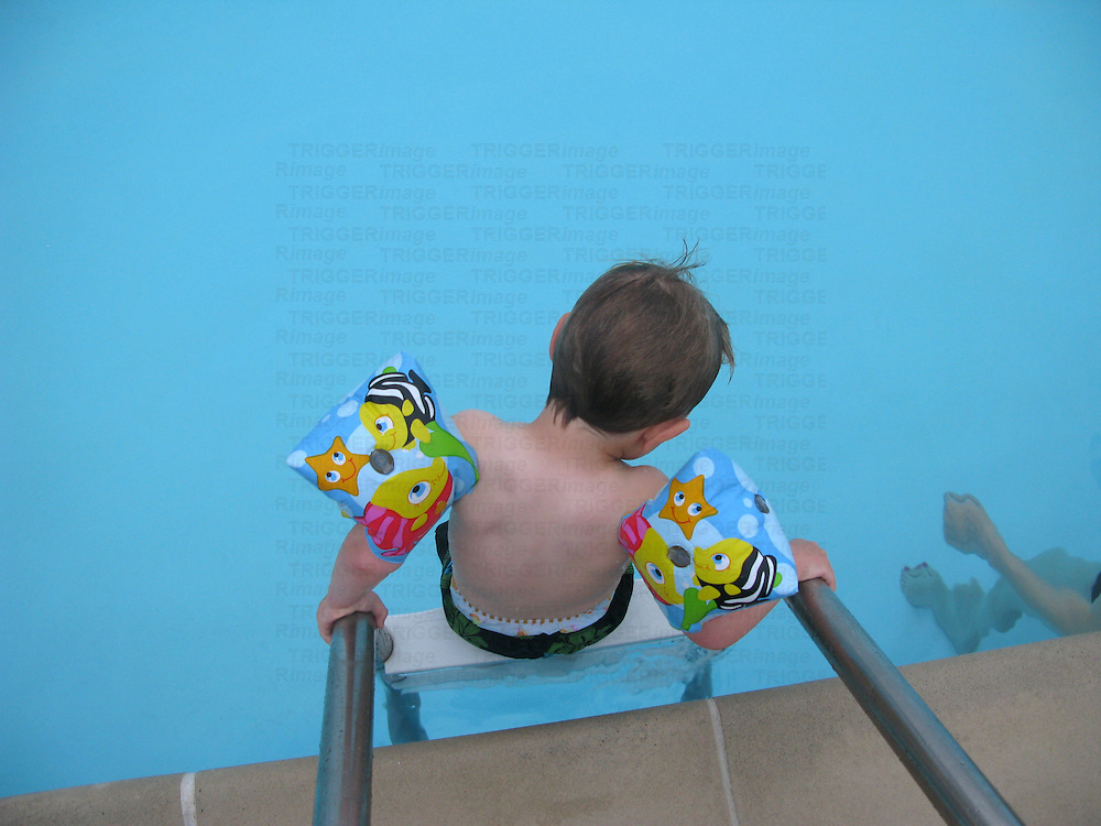 A small child stepping into a swimming pool wearing inflatable armbands
