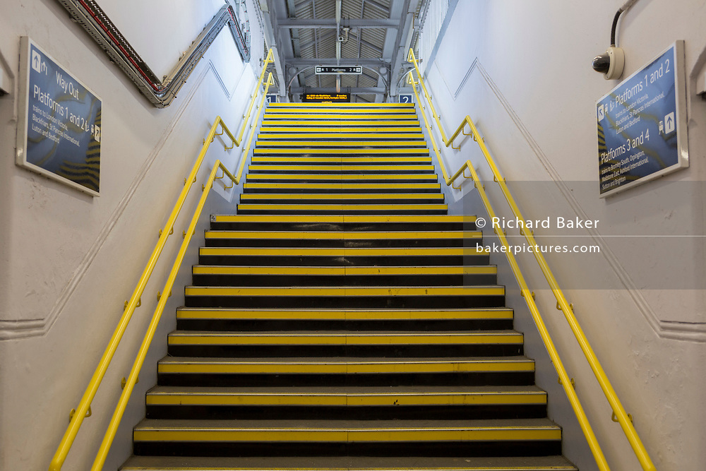 As the second week of the Coronavirus lockdown continues the UK death toll rises by 569 to 2,921, with 1m figure reported cases of Covid-19 being passed worldwide, the empty yellow steps leading up to a platform of Herne Hill rail station in south London, on 2nd April 2020, in London, England.