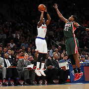 Tim Hardaway Jr. New York Knicks, shoots past Khris Middleton, Milwaukee Bucks, during the New York Knicks vs Milwaukee Bucks, NBA Basketball game at Madison Square Garden, New York. USA. 15th March 2014. Photo Tim Clayton