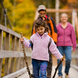 A young girl (age 6) hikes with her parents on a suspension bridge in New Hampshire's White Mountain National Forest.  Lincoln Woods Trail.