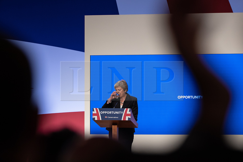 © Licensed to London News Pictures . 03/10/2018. Birmingham, UK. Prime Minister THERESA MAY takes a sip from a glass of water during audience applause as she delivers the Leader's Speech . Day 4 of the Conservative Party conference at the ICC in Birmingham . Photo credit: Joel Goodman/LNP