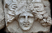 Mask and garland frieze from the Portico of Tiberius on the Southern portico of the Agora, 1st century AD, Aphrodisias, Aydin, Turkey. The Sculpture School at Aphrodisias was an important producer of carved marble sarcophagi and friezes from the 1st century BC until the 6th century AD. The Portico of Tiberius was built under the reign of Tiberius and has many examples of mask and garland friezes, consisting of the heads of gods, goddesses, theatrical characters, mythological figures or masks, each with a distinct facial expression, between hanging garlands of leaves, fruit and flowers. This example shows a smiling, happy woman. Aphrodisias was a small ancient Greek city in Caria near the modern-day town of Geyre. It was named after Aphrodite, the Greek goddess of love, who had here her unique cult image, the Aphrodite of Aphrodisias. The city suffered major earthquakes in the 4th and 7th centuries which destroyed most of the ancient structures. Picture by Manuel Cohen
