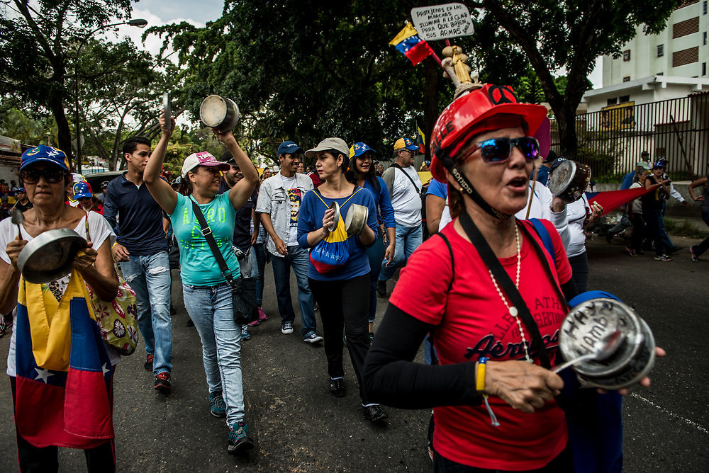 CARACAS, VENEZUELA - JUNE 3, 2017: Anti-government protesters bang empty pots and pans during a peaceful demonstration to show discontent about the current economic situation  and widespread food shortages in Venezuela.  Inflation hit 800% in December of last year &ndash; causing food prices to skyrocket to a price unattainable even for full-time employed professionals.  Over 90 percent of Venezuelans in a recent survey reported not having enough income to buy all the food they need. 73 percent reported involuntarily weight loss of an average of nearly 9 kg each. <br /> The streets of Caracas and other cities across Venezuela have been filled with tens of thousands of demonstrators for nearly 100 days of massive protests, held since April 1st. PHOTO: Meridith Kohut