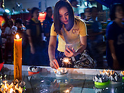 25 NOVEMBER 2015 - BANGKOK, THAILAND:  A Thai woman floats her krathong in a small pool at the temple during Loy Krathong at Wat Yannawa in Bangkok. Loy Krathong takes place on the evening of the full moon of the 12th month in the traditional Thai lunar calendar. In the western calendar this usually falls in November. Loy means 'to float', while krathong refers to the usually lotus-shaped container which floats on the water. Traditional krathongs are made of the layers of the trunk of a banana tree or a spider lily plant. Now, many people use krathongs of baked bread which disintegrate in the water and feed the fish. A krathong is decorated with elaborately folded banana leaves, incense sticks, and a candle. A small coin is sometimes included as an offering to the river spirits. On the night of the full moon, Thais launch their krathong on a river, canal or a pond, making a wish as they do so.    PHOTO BY JACK KURTZ