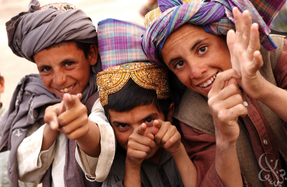 Afghan children jokingly gesture at U.S. soldiers on patrol May 12, 2002 near the Kandahar airfield in southern Afghanistan. U.S. soldiers routinely patrol the area as part of the ongoing coalition Operation Enduring Freedom.