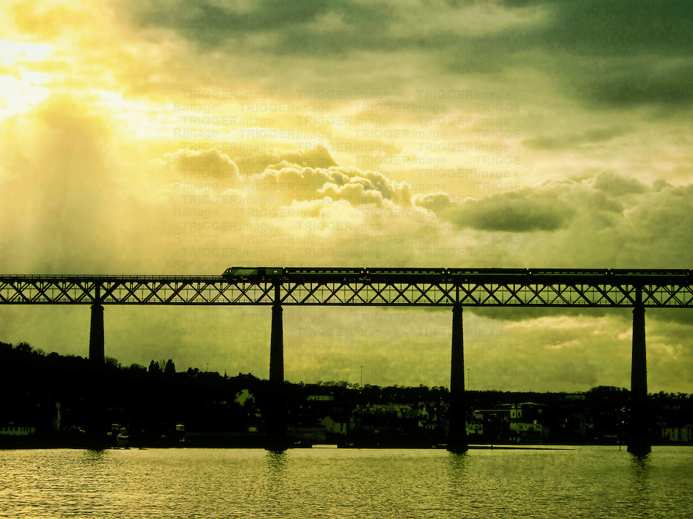 A train and bridge silhouetted against a cloudy sky