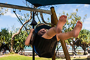 2 year old girl swinging on a swing set, feet in the air