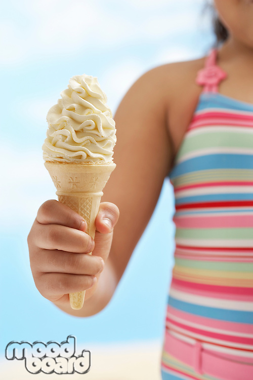 Girl (7-9 years) holding icecream mid section